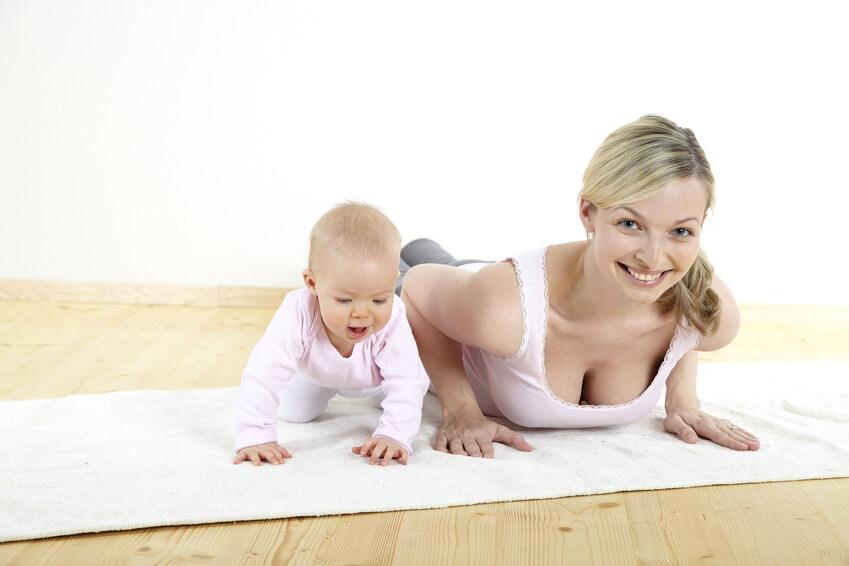 junge huebsche mutter trainiert ihren koerper gemeinsam mit ihrem 7 monate alten baby