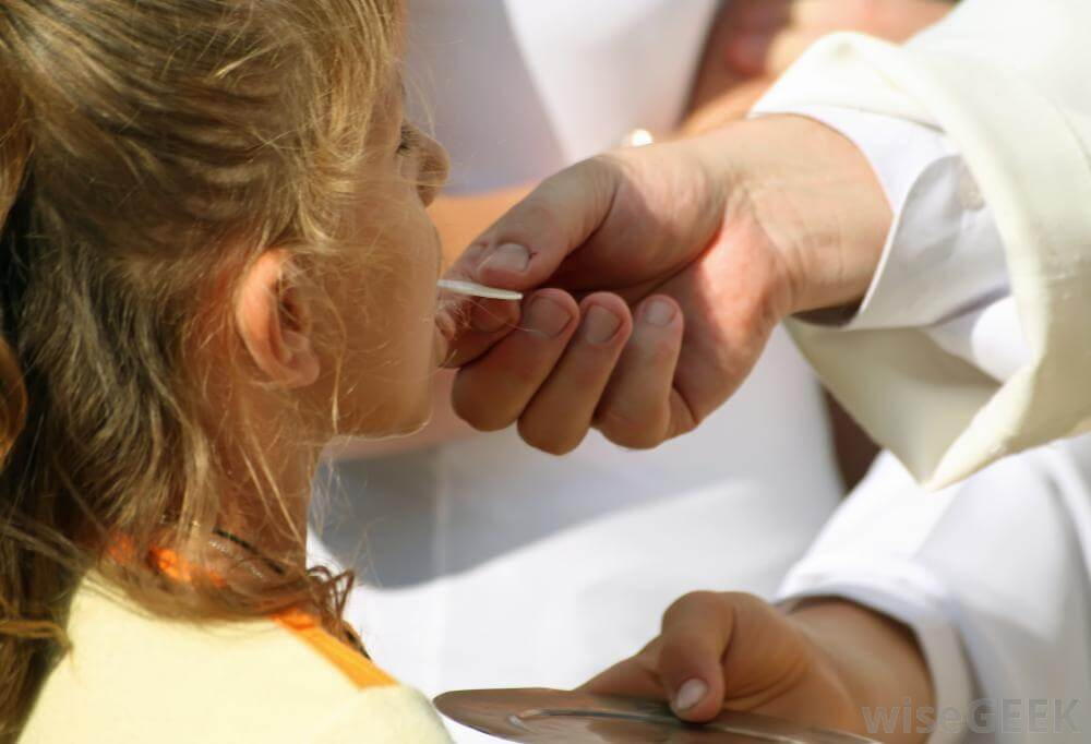 priest-giving-communion-to-a-young-girl
