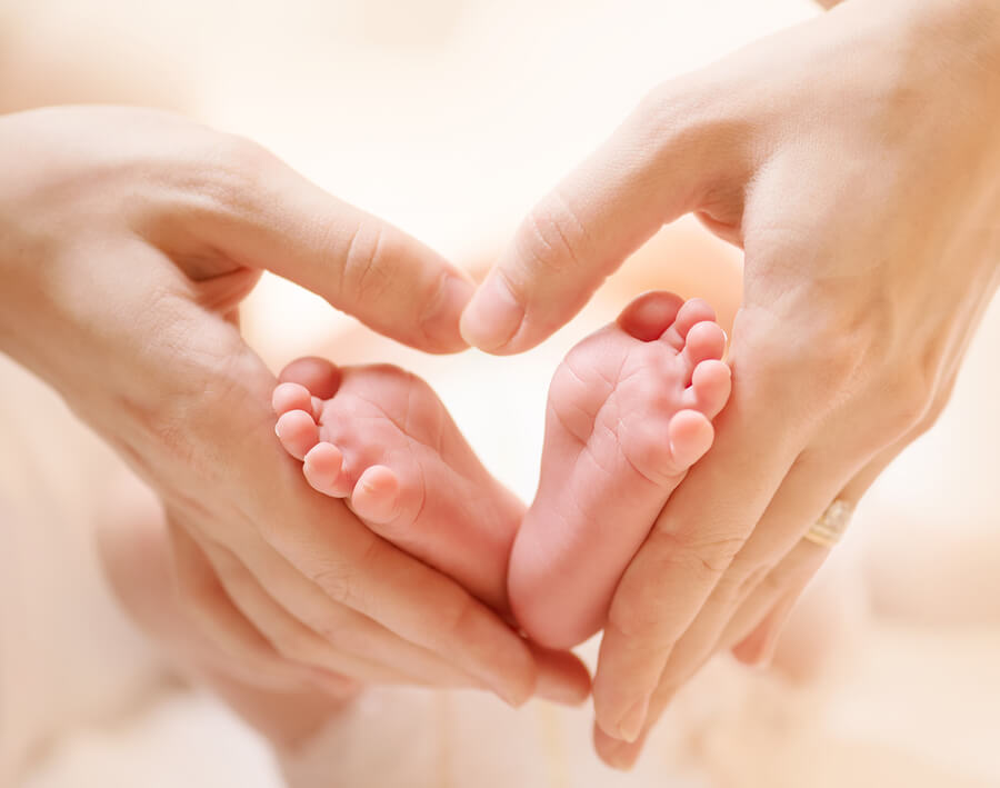Baby feet in mother hands. Tiny Newborn Baby's feet on female Heart Shaped hands closeup. Mom and her Child. Happy Family concept. Beautiful conceptual image of Maternity