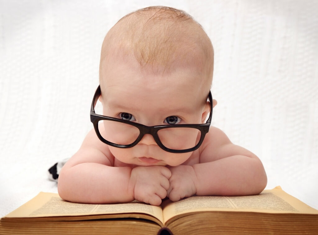 close-up of adorable baby in glasses lying on an old book and light background