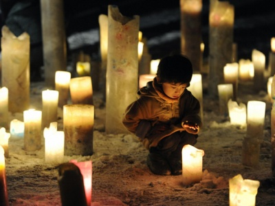 A child looks at a candle flame during an event to pray for the reconstruction of areas devastated by the March 11, 2011 earthquake and tsunami, in Iwanuma in Miyagi prefecture, an area hit by the disaster, in this photo taken by Kyodo January 11, 2012.  Mandatory Credit REUTERS/Kyodo   (JAPAN - Tags: DISASTER SOCIETY) FOR EDITORIAL USE ONLY. NOT FOR SALE FOR MARKETING OR ADVERTISING CAMPAIGNS. THIS IMAGE HAS BEEN SUPPLIED BY A THIRD PARTY. IT IS DISTRIBUTED, EXACTLY AS RECEIVED BY REUTERS, AS A SERVICE TO CLIENTS. MANDATORY CREDIT. JAPAN OUT. NO COMMERCIAL OR EDITORIAL SALES IN JAPAN