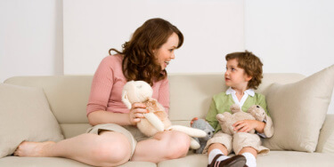 Mother and daughter sitting on sofa with stuffed animals