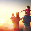 happy family at sunset. father, mother and two children daughters having fun and playing in nature. the child sits on the shoulders of his father.
