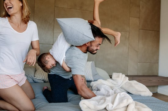 Family playing together on bed at home. Little boy playing with his parents in bedroom.