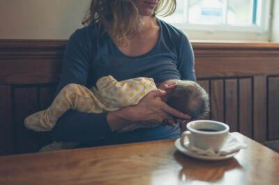 woman-breast-feeding-in-front-of-coffee-mug-in-cafe