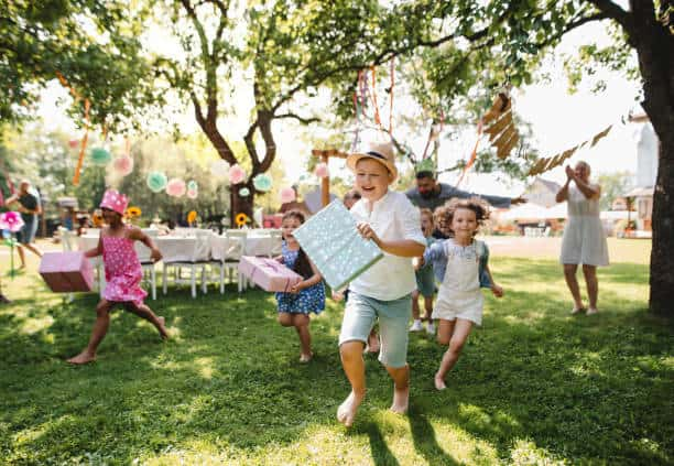 Small children ruunning with present outdoors in garden on birthday party, playing.